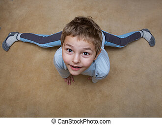 Little boy doing gymnastics on the floor