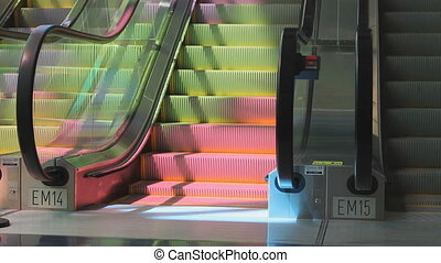 Colourful escalator. - Escalator in pink and yellow light.