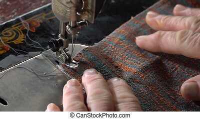 Seamstress sews on a sewing machine. Slow motion - An...