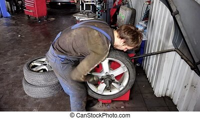 Mechanic balancing a car wheel on an automated machine checking