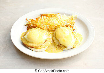 Eggs benedict and hash brown potatoes.