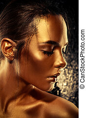 brilliance of gold - Beauty concept. Close-up portrait of a...