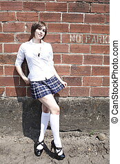A young and pretty woman wearing a plaid skirt next to a...