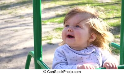 Cute adorable baby girl on swing in summer time in slowmo -...