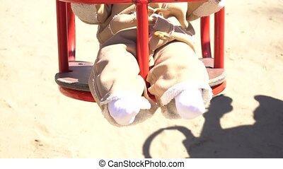 Legs of adorable baby girl on swing