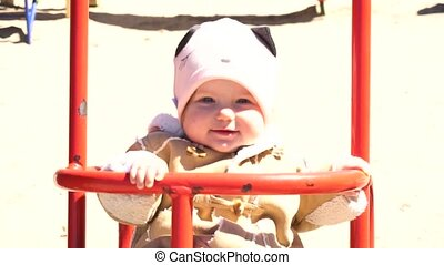 Smiling adorable baby girl on swing in slowmo - Smiling...