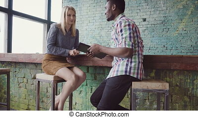 Two colleagues meeting at office to discussing plans. African businessman and caucasian businesswoman look documents.