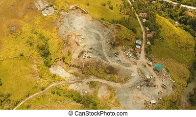 Excavator loads truck in quarry. Philippines,Bohol. -...