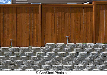 Wood Fencing on Cement Stack Stone Retaining Wall - Wood...