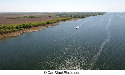 Aerial shot of the Dnipro river with curvy coastline, moving motorboat in spring