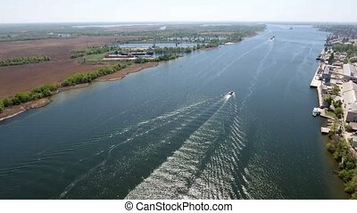 Aerial shot of a powerful motorboat moving in the center of the Dnipro in spring