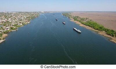 Aerial shot of three huge barges moving up the Dnipro river in spring
