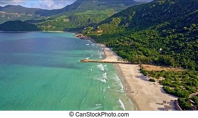 Aerial View over Azure Sea along Sand Beach against Green...