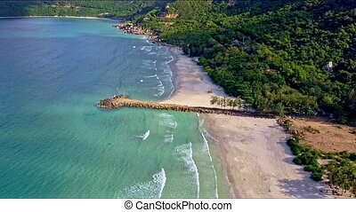 Flycam Moves from Azure Ocean to Sand Beach with Pier -...