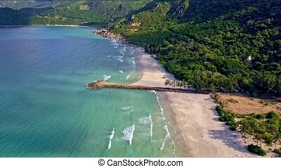 Drone Flies along Azure Sea to Sand Beach by Green Hills -...
