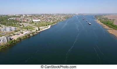 Aerial shot of the Dnipro with several long barges in a sunny day in spring