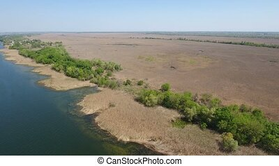 Aerial shot of the Dnipro with a river bank covered with brown weeds in spring