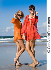 two beautiful women hearing shells on beach