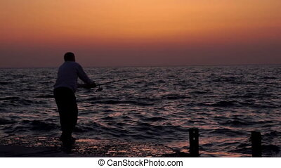 Fisherman sunset sea - Fisherman catches a big fish on the...
