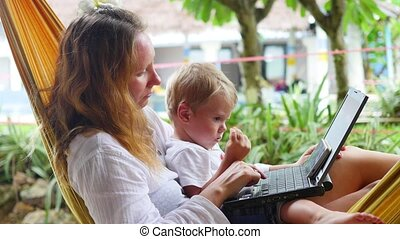 girl and child working on laptop and smartphone lying in a...