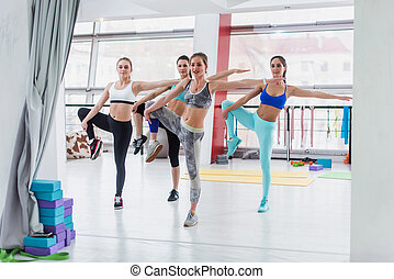 Group of slim Caucasian girls standing in one-leg stance during workout class in gym