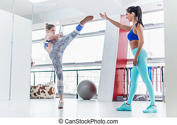 Young Caucasian woman training with a personal trainer in...