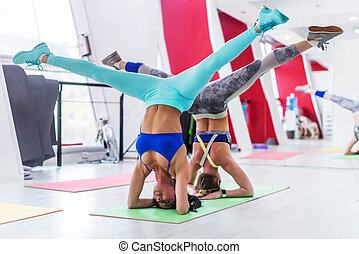 Girls working out together doing wide leg headstand,...