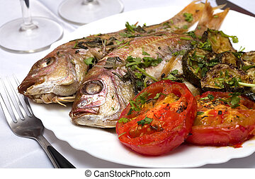 Two Grilled fish with vegetables and herbs on the dish