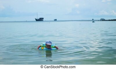 A happy child swims in an inflatable circle in the sea
