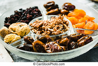 Assorted dried fruits and nuts on a glass plate.Dates, figs,...