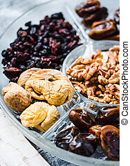 Assorted dried fruits and nuts on a glass plate. Close up. -...