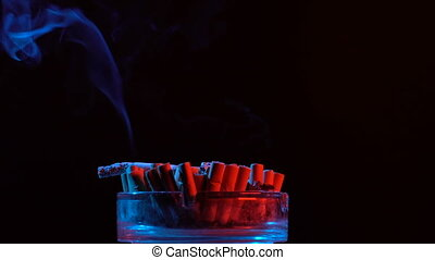 Smoldering cigarette in an ashtray rotate on a table