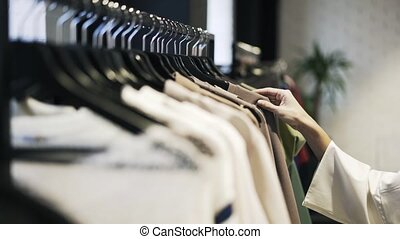 Young woman s hand choosing clothes in a shop