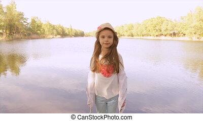 Little girl in a warm sunny day near a lake - Little girl...