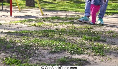 First steps of baby girl in park