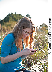 teenage girl - A female teenage girl playing with her cell...