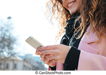 Cropped image of smiling woman using smartphone