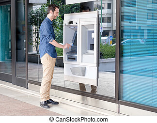 Man hand inserting a credit card in an atm - Man using his...