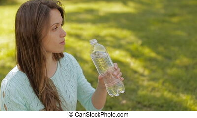 A girl in nature drinking water from a plastic bottle - A...
