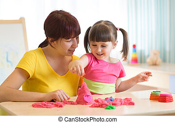 Child play with kinetic sand - Woman and child play with...