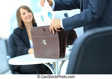 Cropped image of business woman getting documents out of...