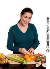 Woman in kitchen peeling orange - Beautiful happy woman in...