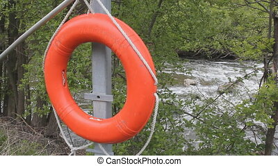 Lifesaver ring by river - Orange lifering with rushing river...