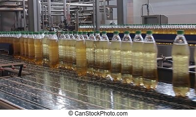 Production process. A conveyor of plastic bottles filled...