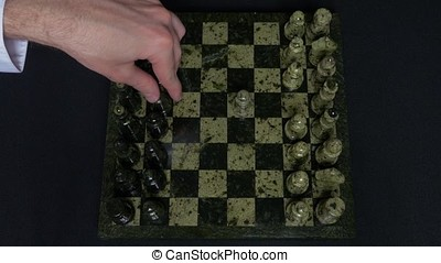 Checkmate. Start Of A Chess Game,the Figures Are Lined Up And A Person Makes The First Move. Hand moving a knight chess piece on chessboard. Man's hands play chess, checkmate in chess