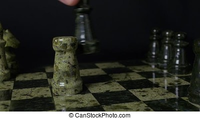 Black Queen in chess defeats white rock. Chess the queen wins victory over the game. Detail of chess piece on black background. Selective focus