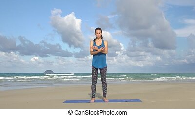 Young woman practicing yoga on the beach in front of sea. Healthy active lifestyle concept.