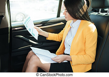 Side view of a concentrated businesss woman analyzing...