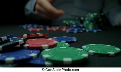 Close-Up of Man Throwing a Poker Chips in slow motion. Close-up of hand with throwing gambling chips on black background. Poker player increasing his stakes throwing tokens onto the gaming table.