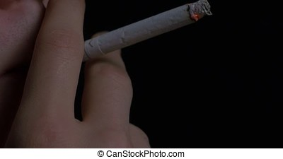 Man smoking cigarette on black background. Close up portrait...